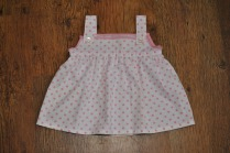 "Cotton pink polka-dot dress edged in pink jersey. Shoulder straps secure with button fastening. Chest size 20/21"", approximately 12-18 months. £16 + p&p."