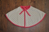 Girl's minky/jersey cape. Secures with plastic snapper and has a decorative bow under the chin. Size 0-1 year. £24 + p&p.