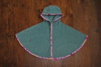 Girl's basic single layer seafoam green fleece poncho edged with pink jungle print bias binding, secures with plastic snappers under the arms. Size 0-3 months. £16 + p&p.