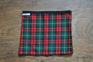 "Girls tartan, pleated 'kilt' skirt. This skirt is made with polyviscose, and not wool, so it is machine washable and softer against the skin. It closes with a popper and a button, both of which can be moved along the inner front panel to increase the life of the skirt. For waist size 18/19"", approximately 3-6 months. £12 + p&p."
